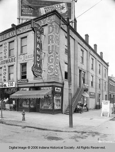 Shandy's Dugstore was at Third Street and Wabash Avenue in Terre Haute, Ind. A billboard advertising Wrigley's spearmint gum is prominent in the backgound. 1925, Terre Haute, Indiana.