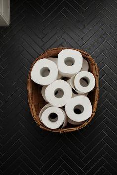 Lägg toalettpappersrullarna i stor flätad korg. Lättar upp strama badrummet och bryter fint mot mörkt golv.