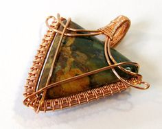 Green opal is the name for this wonderfully marbled variety of chalcedony. I love the rich emerald color and how well it blends into the mottled browns and tans throughout the stone. The copper wire weave on this is generally angular, to suit the stone, with just a couple of rounded swoops to make things interesting. The back of this pendant is just as symmetrical as the front and is designed to sit smoothly and evenly when worn. The warm colors promise to be flattering with many skin tones…