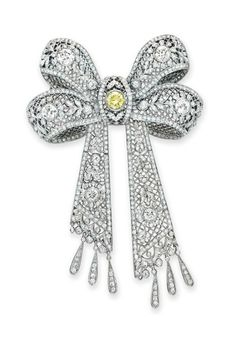 A DIAMOND AND COLORED DIAMOND BOW BROOCH  Designed as an openwork circular and old European-cut diamond ribbon bow, set at the center with a circular-cut yellow diamond, mounted in 18k white gold