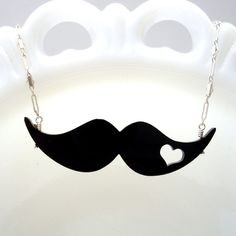 Mustache Love Necklace $35.99 A fabulous laser cut mustache with a little heart cut out ... kind of a little tattoo for your 'stache. The black acrylic mustache is 2.5 inches long, and the necklace is finished with a vintage inspired sterling silver chain. The necklace is adjustable 16-18 inches. Handmade by Isette. Design and Victoriana with a twist of Whimsy.