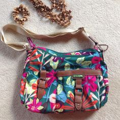 Lilly Bloom multi color crossbody/shoulder bag This durable bag is oh so handy! The exterior has a zipped outer gusseted pocket as well as a slip pocket with snap strap closure. The back has a smaller zip pocket. Two top zips: one opens to a roomy compartment with an interior zip pocket, the other opens to a compartment with two slip pockets, one with a strap closure. Brand, known for using recycled materials in fun patterns. Barely used for a short vacation. Holds all your essentials! Faux…