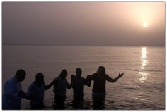 Prayer during the baptism service in the ocean in front of the MOHI missionary compound