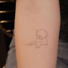 Single needle puppy tattoo on the left inner forearm.