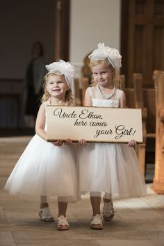 "White tulle flower girl dress idea - tea-length tulle flower girl dresses matching headbands + flower girls carrying sign that says ""Uncle Ethan, here comes your girl!"" {Jessie Moore Photography}"