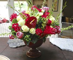Not your typical flower arrangement: a mix of red & white roses, green coffee bean berries, green orchids, pink protea, red ginger & heart-shaped anthuriums.