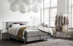 A light bedroom with a grey bed and two white bedside tables with table lamps.