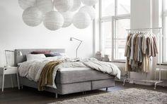 Vaalea makuuhuone, jossa harmaa sänky ja kaksi valkoista yöpöytää valaisimineen.
