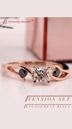 This 3 stone engagement ring displays a princess cut lab diamond in the center. Alluring round cut black diamond is encrusted excellently in tension setting on each side of the center stone on the lustrous rose gold metal for an elegant look. #fascinatingdiamonds #labdiamond #labdiamondring #rings #rosegoldengagementring #engagementring #threestoneengagementring #threestonering #womensfashion #trendingmetal #womensjewelry Three Stone Engagement Rings, Three Stone Rings, Rose Gold Engagement Ring, India Jewelry, Gold Jewelry, Jewelry Accessories, Women Jewelry, Black Diamond, Diamond Rings