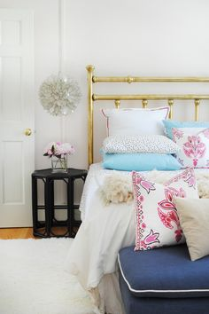 Girl's bedroom with brass bed, blush pink walls, black, navy blue, and pink plus a DIY Moroccan wedding blanket