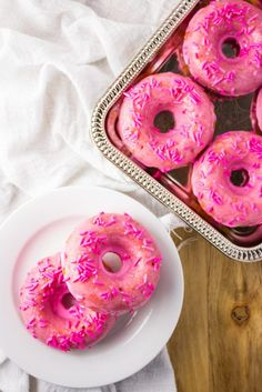 Strawberry Donuts - An easy recipe for baked strawberry donuts covered in a pink tinted glaze and sprinkles. It is love at first bite. http://simplylakita.com #donuts