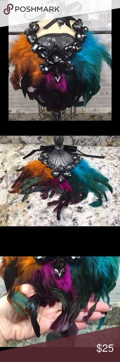 """Multi-colored Feather with Crystal Necklace What a stunning piece to wear to any event including a New Year' Eve celebration! Pair it with a variety of colors, or your favorite little black dress. Crystal stones are a charcoal grey and the necklace ties in the back with a gross grain ribbon. Entire design measures approximately 9""""x9"""". Bedecked & Bedazzled Jewelry Necklaces"""