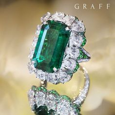 An exceptional 11.76 carat emerald cut Colombian emerald ring, incorporating 6.65 carats of the finest diamonds,