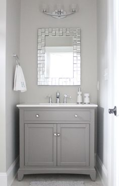 Grey and white bathroom with mirror. Paint color: Repose Gray by Sherwin Williams