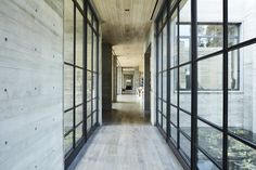 A view of a glass-walled corridor. Modern homes are somewhat rare in Malibu, where Cape Cod style houses are prevalent.