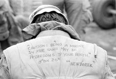 """A U.S. Marine shows a message written on the back of his flack vest at the Khe Sanh combat base in Vietnam on Feb. 21, 1968 during the Vietnam War. The quote reads, """"Caution: Being a Marine in Khe Sanh may be hazardous to your health."""" Khe Sanh had been subject to increased rocket and artillery attacks from the North Vietnamese troops in the area."""