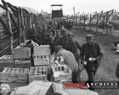 World War II Photograph: German prisoners on arrival in England for transfer to a prisoner of war camp, queue up for US Army rations. England. 11 June 1944.