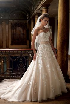 """Brides.com: Wedding Dresses We Love For Under $1,500. Blush tones and graphic lace take a classic (and slimming) strapless A-line out of traditional territory.   Style 213247, """"Hillary"""" organza and lace wedding dress, $1,235, David Tutera for Mon Cheri  See more David Tutera for Mon Cheri wedding dresses."""