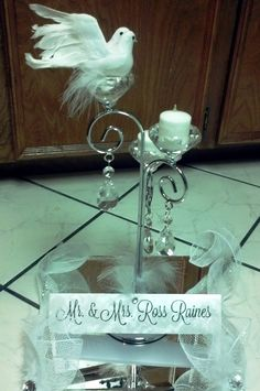 This was the sweetheart table arrangement at the reception. I found this beautiful silver candle holder at Hobby Lobby and hot glued the doves to the top candle holder as a symbol of God's Holy Spirit that has and will continue to bless and guide them. I created a name card for them using a beautiful wedding font I downloaded for free. Finally, I added some of the white deco mesh to the sides of the mirror to dress it up a little more. It was so fun preparing for the wedding.