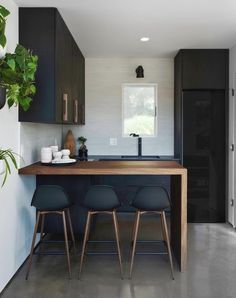 Loving every detail of this design by for including a stunning walnut waterfall counter and our Wildwood Sconce in matte black. Black Kitchen Cabinets, Black Kitchens, Home Kitchens, Small Kitchens, Kitchen Island, Cottage Kitchens, Modern Kitchens, Modern Kitchen Design, Interior Design Kitchen