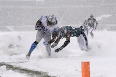 Detroit #Lions' Joique Bell, left, is tackled into the #snowbowl2013