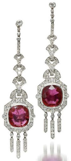 A pair of art deco ruby and diamond pendant earrings, Mauboussin, 1924. Each designed as an oval-shaped ruby within an old European-cut diamond surround suspended from a geometric line of old European-cut diamonds; with maker's mark, rubies each weighing approximately: 4.45 carats; mounted in platinum.