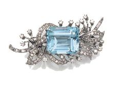 N AQUAMARINE, DIAMOND AND BAGUETTE DIAMOND FLORAL SPRAY BROOCH  set with a large rectangular step cut aquamarine within diamond set leaves and single stone buds in articulated mounts with baguette diamond stem, with twin prong clip brooch fitting.