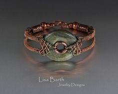 This unique bracelet is hand woven in solid copper. There is a double criss cross harness of sorts that holds the green Jasper stone. This bracelet is quite striking when worn and gets noticed quite a bit. The woven sides can be molded to fit your wrist for comfort. This bracelet