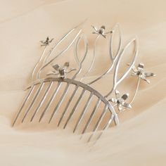 Enhance the beauty of you and your hair with the sterling silver Malena comb. With its organic design and cubic zirconia studded flowers, it is a delicate and graceful piece perfect for any fairytale wedding.