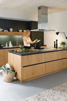 Holz bringt Wärme in die Küche und lässt sich hervorragend mit Schwarz kombinieren. Diese Holzküche hat nicht nur eine schwarze Arbeitsplatte, auch die Blenden sind schwarz gehalten. #kueche #küchen #küchendesign #holzküchen #kitchen #kitchendesign American Kitchen, Kitchen Handles, Wooden Kitchen, Black Kitchens, Living Area, Modern Kitchen Design, Kitchen Interior, Home Goods, Country Kitchen
