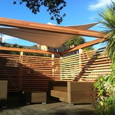 Create an outdoor contemporary room with Sail Shades & wooden trellis walls