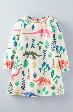 Mini Boden 'Florasuarus' Smock Dress (Toddler Girls, Little Girls & Big Girls). Bright, colorful dinosaurs roam over a darling smock dress styled with long sleeves and elasticized cuffs.