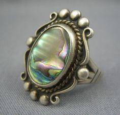 Here is a beautiful vintage ring from the 1930s with a classic old Bell Trading post design set with a thick glowing abalone cab instead of the usual turquoise. Turquoise was difficult to come by during the depression era and much of the Southwestern tourist jewelry you see from that era has alternative settings like art glass or less expensive stones to make it more affordable for tourists. It is marked sterling and has the Bell Trading Post hallmark and it's in perfect shape.