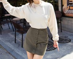 The big buttons on this classic button down skirt will add interest to your overall aura. Team with a cozy long sleeved tee and ankle boots. -High waist -Button down -Side pockets -Straight cut -Mid-thigh length -Available colors: white, khaki