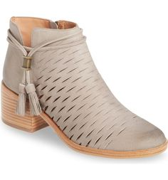 Slim slits add breathable comfort to this versatile and chic leather bootie lofted by a chunky stacked heel.