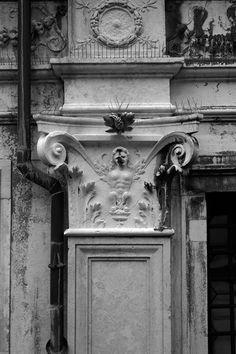 """Palazzo dei Camerlenghi. Decorazione licenziosa del capitello. Decorazione licenziosa del capitello di un pilastro a lato dell'ingresso. Figura allegorica di sesso femminile con """"la natura in fiamme"""" a causa di una scommessa"""