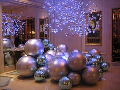 Paint big balls from Walmart in metallics then hang glass balls(which go on sale after the holidays) in a cluster
