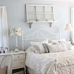 White wooden night stand, wrought iron bed, repurposed window/display