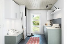 A pink geometric patterned rug brings a splash of color to this soft grey utility room. Slouchy pillows on the storage/seating area give it softness and warm.