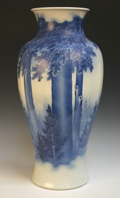 An impressive Japanese blue and white porcelain vase by Makuzu Kozan, circa 1900, the elegantly thrown upright baluster body painted in tones of underglaze blue with a misty forest landscape of pines and cedars near and far receding into the mists, bold five character seal mark in underglaze blue within incised double circle to base, height approx 60cm (vertical hairline crack to body).