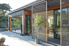Exterior wooden cladding and slats. Move along tracks to block the sun throughout the day