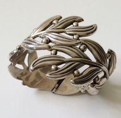 This beautiful Modernist, stylized leaf and berry clamper bracelet designed by Margot de Taxco was crafted from her molds by her protégé and master silversmith Hilario Lopez. Hilario was entrusted with the molds after Margot closed her workshop in 1978. The Sterling silver bracelet opens with a hinge with great tension, and wears very comfortably on most wrists. It measures 2 wide and 56 grams, marked HL 925 Taxco Sterling Mexico eagle assay 3. Excellent condition.