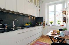 White cabinets, black countertops, black backsplash, neutral floor
