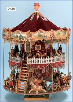 Huge two-story toy carousel.  Size: 82 cm high, 60 cm diam.  Ca. 1900  Made from wood / dough figurines, horse riders, benches, Zinngeländer, velvet walls, embroidered beads, paneling, painted pressboard.