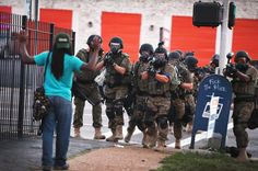 Police force protesters out of the business district of Ferguson, Missouri, on August 11, 2014.