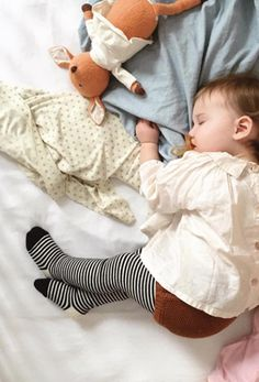 Boho babe sleeping sweetly in chic little layered outfit. Black and white striped tights perfect little baby accessory. Sustainably made from organic cotton for Noble Carriage by Goat-Milk.
