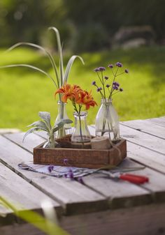 Create a handsome centerpiece with a small wooden tray and bottles of various sizes. Orange lilies and purple tail verbena offer contrasts in color and shape.