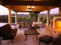 The outdoor living area uses a mixture of stones and columns to create a Tuscan feel. An outdoor kitchen is on a lower level that overlooks a stunning view.
