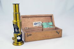 This Antique Microscope comes with it's original box and two slides. This is a compound barrel microscope made of brass with a reflecting mirror.   The slides are original and are of a Fly's wings and something else. The slide paper is robin's egg blue. The slides look to be Victorian a