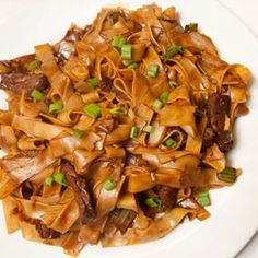 Beef Chow Fun  250g (1/2 lb) dried wide rice noodles  3 Tbsp dark soy sauce  2 tsp dry sherry or Chinese rice wine  1 tsp cornstarch  250g (1/2 lb) flank steak, thinly sliced across the grain  118mL (1/2 c.) beef broth  2 tsp oyster sauce  2 Tbsp vegetable oil  1 medium onion, sliced  3 green onions, cut into 1-inch pieces  recipe from Martin Yan